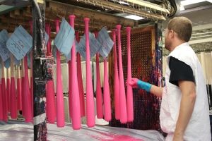 Louisville Slugger Factory worker checks pink bats as they dry after being dipped.